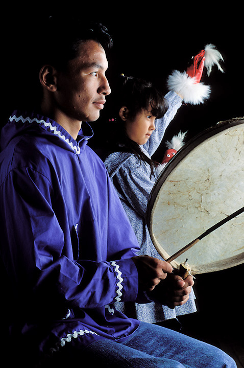 Iñupiaq man in traditional kuspuk drums on traditional drum while young girl dances with dance gloves