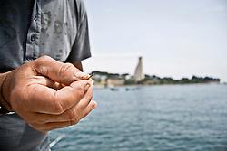 Un pescatore al Porto di Brindisi prepara l'amo della sua canna da pesca con allo sfondo il Monumento al Marinaio in viale Duca degli Abbruzzi. 29/05/2010 PH Gabriele Spedicato