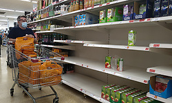© Licensed to London News Pictures. 20/09/2021. London, UK. A shopper walks past nearly empty shelves of cartons fruit juice in Sainsbury's in north London as fears of food shortages grow after two of the UK's biggest Carbon Dioxide (CO2) producers halted production last week due to soaring gas prices. Photo credit: Dinendra Haria/LNP