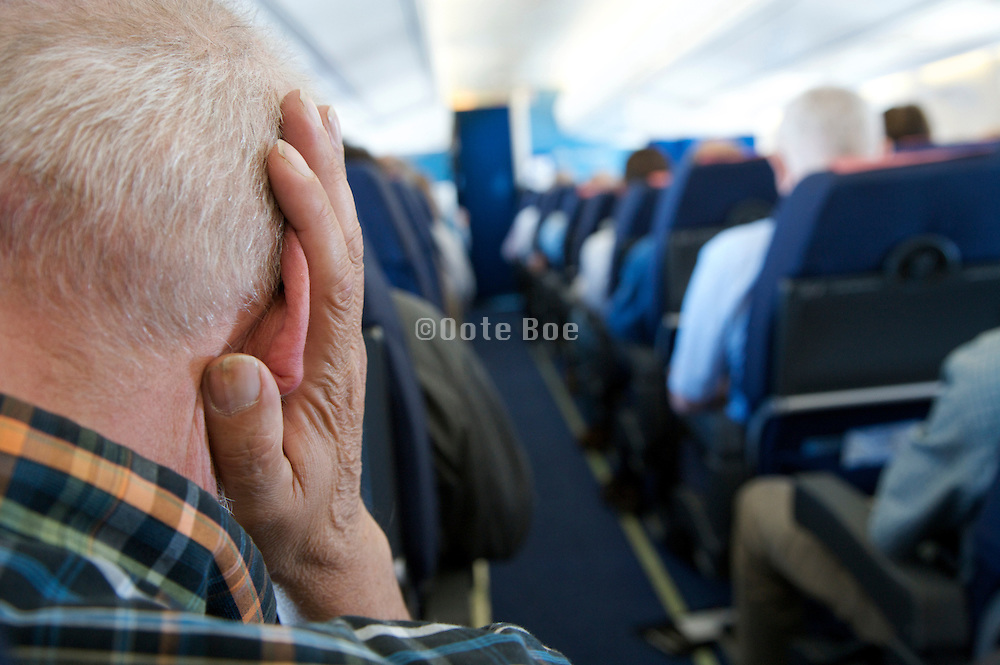 elderly man placing his hand over his ear inside an airplane