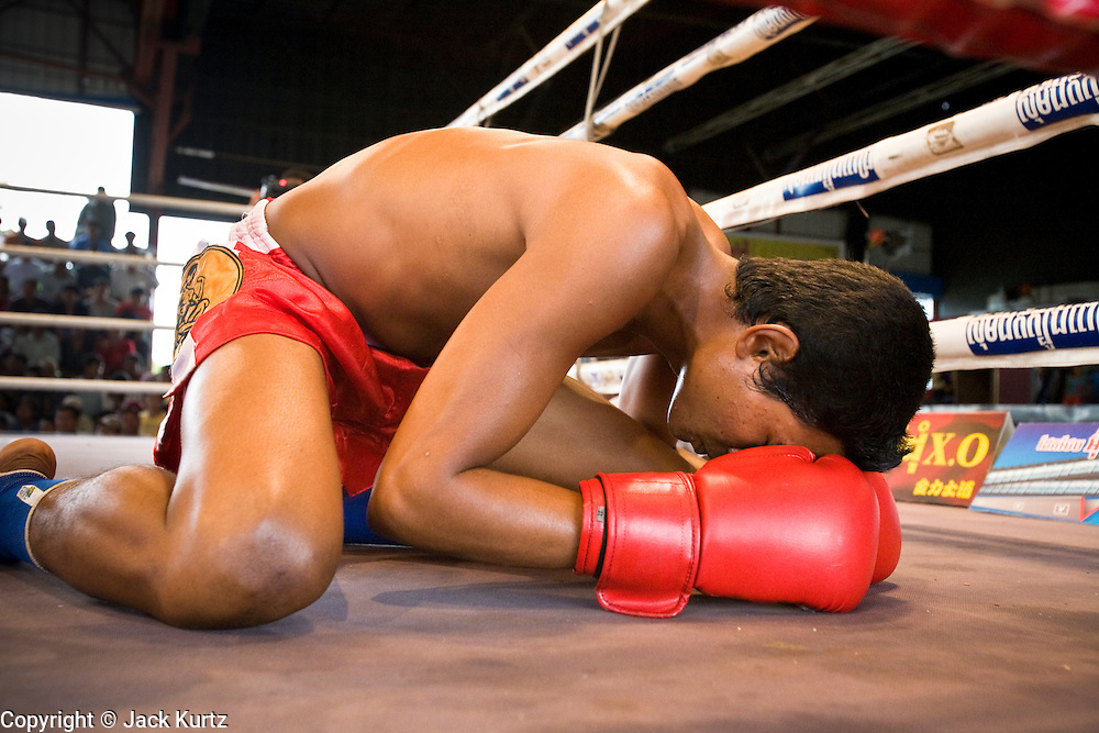 02 JULY 2006 - PHNOM PENH, CAMBODIA: A boxer prays before his bout during a traditional Khmer boxing match in Phnom Penh, Cambodia. Khmer boxing is the same sport as Muay Thai (traditional Thai kick boxing) but because off animosity between Thailand and Cambodia it is called Khmer Boxing in Cambodia. The Cambodians claim to have invented the sport, which is also practiced in Laos and Burma. Photo by Jack Kurtz