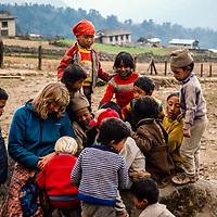 Sherpa children watch a young trekker showing a book in the Khumbu region of Nepal 1986.