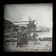 Magic lantern slide of mother and daughter standing by wooden frame of cod fish drying with village in background, Norway, c 1900
