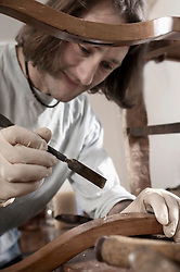 Carpenter applying glue on antique wooden chair at workshop, Bavaria, Germany