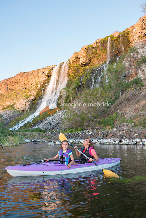 Mother and daughter kayaking under thousand springs water fall at Ritter Island in the Snake River Hagerman, Idaho. MR