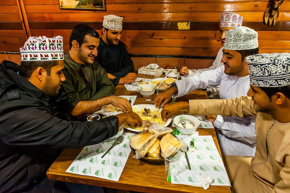 Omani men eating mansaf (the national dish of Jordan), Al-Quds Restaurant, Downtown Amman, Jordan.