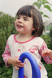 Young girl with autism standing at top of slide in garden smiling,