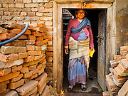 01 MARCH 2017 - KHOKANA, NEPAL: A woman stands in the doorway of her home, destroyed in the 2015 earthquake. Recovery seems to have barely begun nearly two years after the earthquake of 25 April 2015 that devastated Nepal. In some villages in the Kathmandu valley workers are working by hand to remove ruble and dig out destroyed buildings. About 9,000 people were killed and another 22,000 injured by the earthquake. The epicenter of the earthquake was east of the Gorka district.     PHOTO BY JACK KURTZ