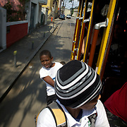 School children ride the Bondinho, tram or trolley car as it heads along the streets of Santa Teresa in the hills of Rio de Janeiro. The trap ride from the City Centre across the Lapa Aquaduct is popular for both tourists and locals. Rio de Janeiro,  Brazil. 20th September 2010. Photo Tim Clayton..