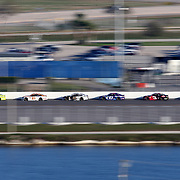 The pack of cars is seen on the backstretch during the 60th Annual NASCAR Daytona 500 auto race at Daytona International Speedway on Sunday, February 18, 2018 in Daytona Beach, Florida.  (Alex Menendez via AP)