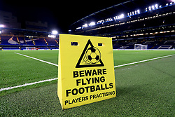 A Beware Flying Footballs sign is put on the pitch whilst the players are practising before the Carabao Cup Semi Final, First Leg match at Stamford Bridge, London.