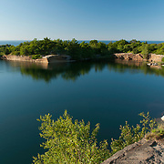 An abandoned granite quarry at Halibut Point State Park in Rockport, MA is full of fresh water. The Atlantic Ocean is just beyond the trees.