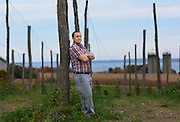 Chris Hansen, partner at Climbing Bines Hop Farm and and hop farmer, stands in the hop yard of the farm in Penn Yan, N.Y., Tuesday, October 25, 2011.  The farm is located near the shores of Seneca Lake, seen in the distance. The bines, which are empty, sold out of it's harvest this year. Climbing Bines supplies regioinal breweries with hops, the majority of which are used for harvest ales. Climbing Bines' two other partners who are not pictured are Brian Karweck and Jerimiah Sprague..(Heather Ainsworth for The New York Times)