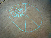 Make Peace Happen chalk drawing on a sidewalk.  Part of the peace symbol is missing to symbolize that more work is needed to achieve peace.