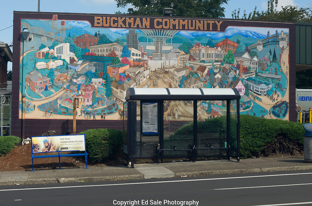 A colorful wall mural of the Buckman community depicting the neighbood is painted on a building wall behind a bus stop on southeast Morrison Street in Portland, Oregon.