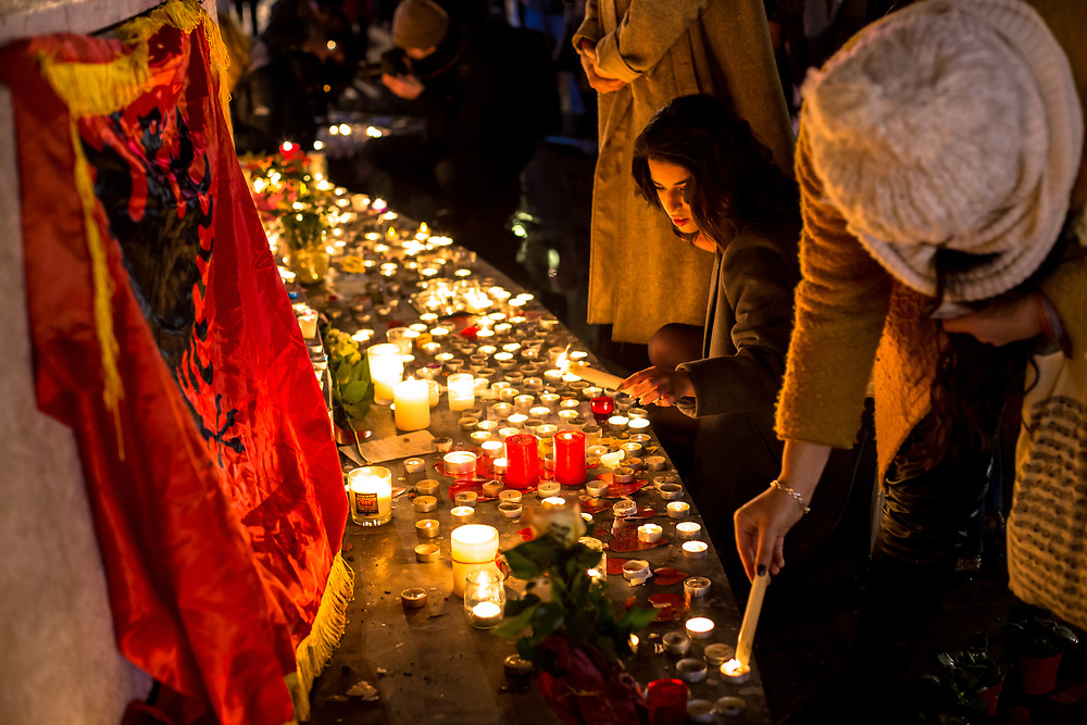 Paris, France.  November 13, 2016.  People light candles at a makeshift memorial in Place de la Republique (Republic Square) to pay tribute to the more than 130 victims of the  Islamic State (ISIS) terrorist attacks which occurred one year before.