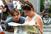 Couple age 28 reading newspaper at Bastille Day celebration.  Minneapolis Minnesota USA