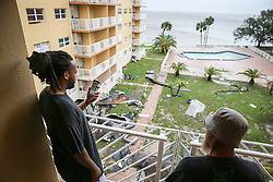 October 7, 2016 - Titusville, Florida, U.S. - WILL VRAGOVIC   |   Times.Brian Farmer, 32, left, and Jason R. Procell Sr., 47, take photos from a balcony overlooking the courtyard in the Bay Towers apartments in Titusville, Fla. on Friday, Oct. 7, 2016. City officials condemned the building after winds from Hurricane Matthew tore large sections of the roof off, and at least 50 people are being displaced. (Credit Image: © Will Vragovic/Tampa Bay Times via ZUMA Wire)