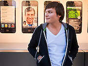 14 OCTOBER 2011 - SCOTTSDALE, AZ:   A man waits in line to buy the new iPhone 4S in front of a display for iPhones at the Apple Store in Scottsdale Quarter. Hundreds of people lined up at the Apple Store in the Scottsdale Quarter in Scottsdale, AZ, Friday, Oct. 14, to buy the iPhone 4S. The phone sold out in pre-orders last week and sales at the Scottsdale Apple Store were brisk through the morning.     PHOTO BY JACK KURTZ