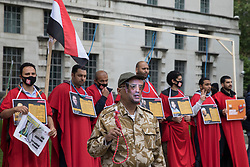 A man wearing a mask featuring an image of General Abdel Fattah el-Sisi and holding a noose stands in front of anti-coup activists with nooses around their necks during a protest opposite Downing Street against political executions in Egypt on the 8th anniversary of the Egyptian military coup against President Mohamed Morsi on 3rd July 2021 in London, United Kingdom. 92 political prisoners have been executed in Egypt since the coup, with death sentences ratified by General Abdel Fattah el-Sisi for a further 64.