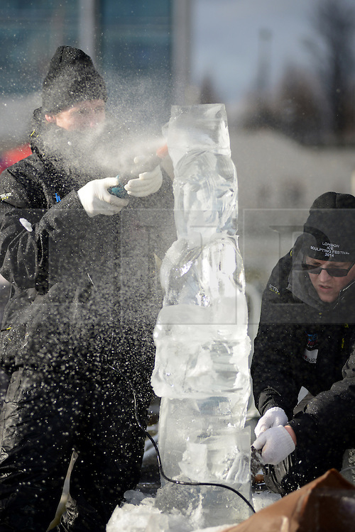 © Licensed to London News Pictures.10/01/2013. London, UK. Members of team Poland create an ice sculpture during the single block ice-sculpting competition at the London Ice Sculpting Festival in Canary Wharf.. Photo credit : Peter Kollanyi/LNP