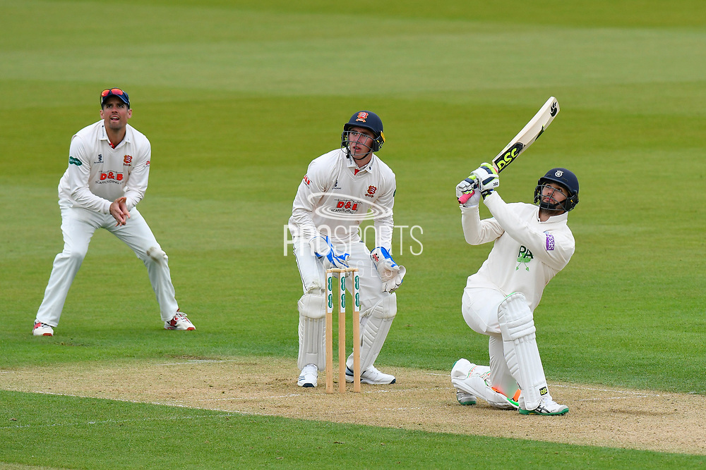 Rilee Rossouw of Hampshire hits the ball over the boundary for six runs watched by Alastair Cook of Essex and Dan Lawrence of Essex during the first day of the Specsavers County Champ Div 1 match between Hampshire County Cricket Club and Essex County Cricket Club at the Ageas Bowl, Southampton, United Kingdom on 5 April 2019.