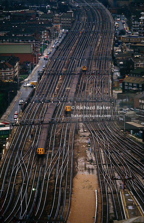 An aerial landscape view of a railway network whose tracks and rails converge on a station in central London. Three trains filled with commuters all make their way into this unseen railway hub. The route curls away into the distance, slicing its way through the capital. London Rail is a directorate of Transport for London (TFL), involved in the relationship with the National Rail network within London, UK. It manages non-tube rail systems in London. Railways started to change the landscape of London itself, followed by its suburbs in the mid to late 19th century when streets and neighbourhoods were cut in half by the new infrastructure.