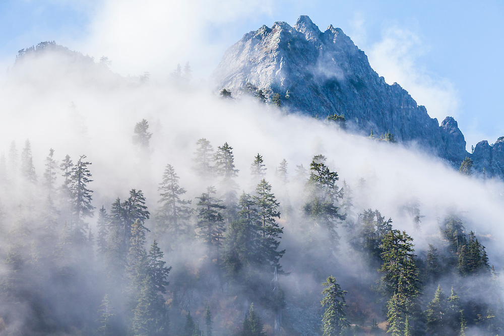Low clouds drift through the forest and mountains (Chair Peak) near Snow Lake at Snoqualmie pass in the Central Cascades of Washington state, USA. Autumn.