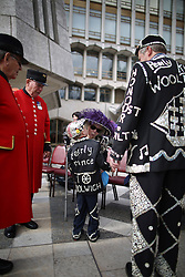 © Licensed to London News Pictures. 27/09/2015. London, UK. The Pearly Prince of Woolwich (C) kisses a family member as Chelsea Pensioners (L) look on in Guildhall Square during a Harvest Festival celebration. Photo credit: Peter Macdiarmid/LNP