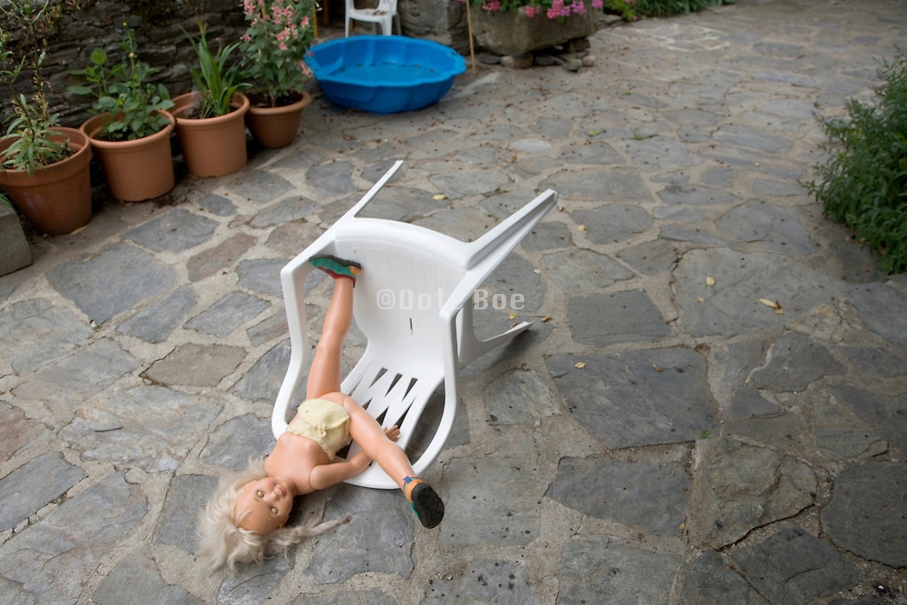 doll laying on the pavement with chair