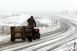 © Licensed to London News Pictures. 28/12/2020. Builth Wells, Powys, Wales, UK.  A farmer rides a quad bike along the B4520 Brecon Road through a wintry landscape on the Mynydd Epynt moorland near Builth Wells in Powys, Wales, UK. Photo credit: Graham M. Lawrence/LNP