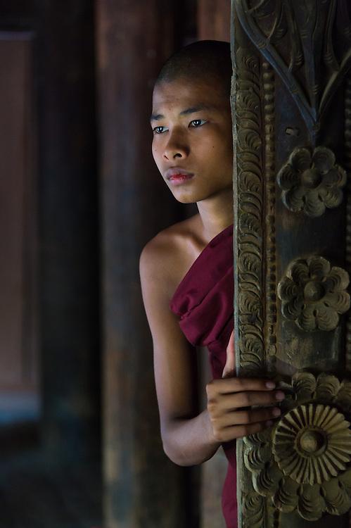 BAGAN, MYANMAR - CIRCA DECEMBER 2013: Young monk peaking through a window in the village of Shwe Kun Cha Hpaya close to Bagan in Myanmar.