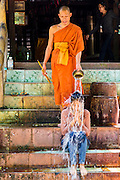 "02 JULY 2013 - ANGKOR WAT, SIEM REAP, SIEM REAP, CAMBODIA:  A Buddhist monk blesses a woman by splashing her with water at a small monastery near the Bayon temple in the Angkor Wat complex. Angkor Wat is the largest temple complex in the world. The temple was built by the Khmer King Suryavarman II in the early 12th century in Yasodharapura (present-day Angkor), the capital of the Khmer Empire, as his state temple and eventual mausoleum. Angkor Wat was dedicated to Vishnu. It is the best-preserved temple at the site, and has remained a religious centre since its foundation – first Hindu, then Buddhist. The temple is at the top of the high classical style of Khmer architecture. It is a symbol of Cambodia, appearing on the national flag, and it is the country's prime attraction for visitors. The temple is admired for the architecture, the extensive bas-reliefs, and for the numerous devatas adorning its walls. The modern name, Angkor Wat, means ""Temple City"" or ""City of Temples"" in Khmer; Angkor, meaning ""city"" or ""capital city"", is a vernacular form of the word nokor, which comes from the Sanskrit word nagara. Wat is the Khmer word for ""temple grounds"", derived from the Pali word ""vatta."" Prior to this time the temple was known as Preah Pisnulok, after the posthumous title of its founder. It is also the name of complex of temples, which includes Bayon and Preah Khan, in the vicinity. It is by far the most visited tourist attraction in Cambodia. More than half of all tourists to Cambodia visit Angkor.         PHOTO BY JACK KURTZ"