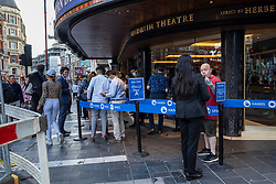 """© Licensed to London News Pictures. 27/07/2021. LONDON, UK.  Audience members line up ahead of the evening performance of """"Les Miserables"""" at the Sondheim Theatre. Evidence of negative Covid tests or proof of double vaccinations are checked prior to entry and facemasks are encouraged. Following """"Freedom Day"""" on 19 July, when the UK government eased lockdown restrictions, the theatre has operated at 50% capacity delivering a modified """"concert version"""" of the well known musical.  Management plans to gradually get back to 100% audience capacity ahead of the full theatrical version to be performed in September.  Photo credit: Stephen Chung/LNP"""