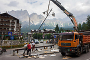 With a backdrop of Dolomites mountains, workmen erect a new lap post in the city of Cortina d'Ampezzo, Veneto, Italy. Cortina d'Ampezzo commonly referred to as Cortina, is a town and comune in the heart of the southern (Dolomitic) Alps in the Veneto region of Northern Italy. Situated on the Boite river, in an alpine valley, it is a popular winter sport resort known for its skiing trails, scenery, accommodation, shops and après-ski scene, and for its jet set and aristocratic European crowd.