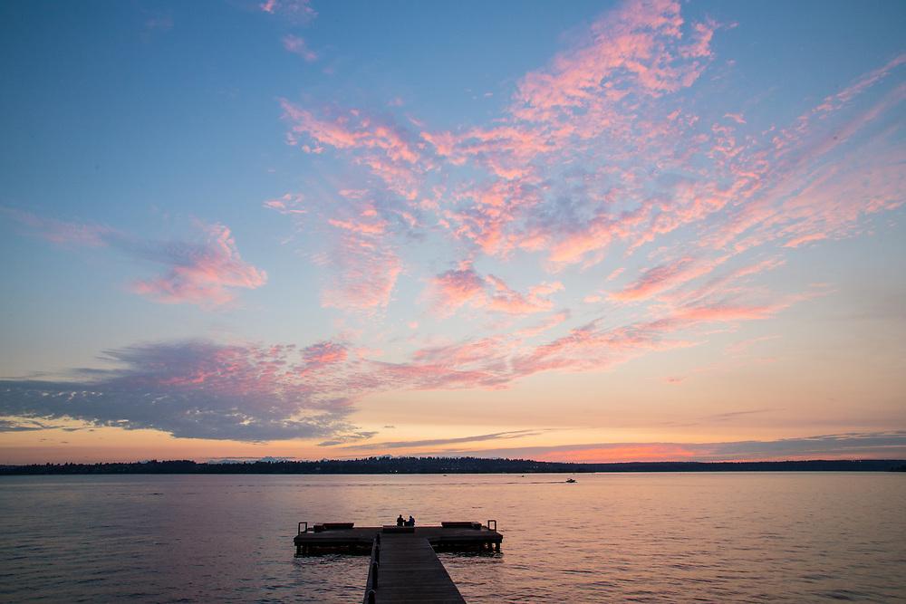 United States, Washington, Kirkland.  couple on pier on Lake Washington at Marsh Park with dramatic sunset