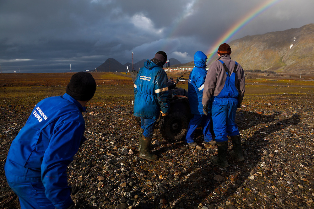 The appearance of a rainbow startles men working outside the Polish Polar Station in Hornsund, Svalbard.