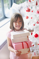 Smiling Young Girl Holding Stack of Christmas Presents