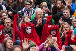 London, UK. 14 October, 2019. The Red Brigade joins fellow climate activists from Extinction Rebellion watching theatrical mock trials, of the UK's financial sector for the crime of ecocide and of the Government for 'criminal negligence' in having permitted it, in front of the Bank of England. Roads were blocked around Bank on the eighth day of International Rebellion protests across London.
