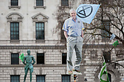 An image of veteran wildlife and environmental broadcaster Sir David Attenborough is held high in Parliament Square next to the statue of Field Marshal Jan Christiaan Smuts, the South African and British Commonwealth statesman, military leader and philosopher, during the week-long protest by climate change activists with Extinction Rebellions campaign to block road junctions and bridges around the capital, on 23rd April 2019, in London England.