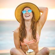 Girl with a coconut laughing at the beach in Mission Beach, San Diego, CA.