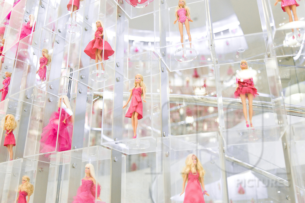 Barbie dolls wearing pink dresses are displayed in translucent shelves. Barbie's shop, Shanghai, China, Asia.