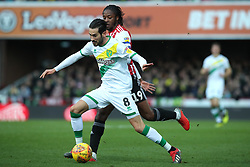 Brentford's Romaine Sawyers (back) and Norwich City's Mario Vrancic battle for the ball during the Sky Bet Championship match at Griffin Park, London.