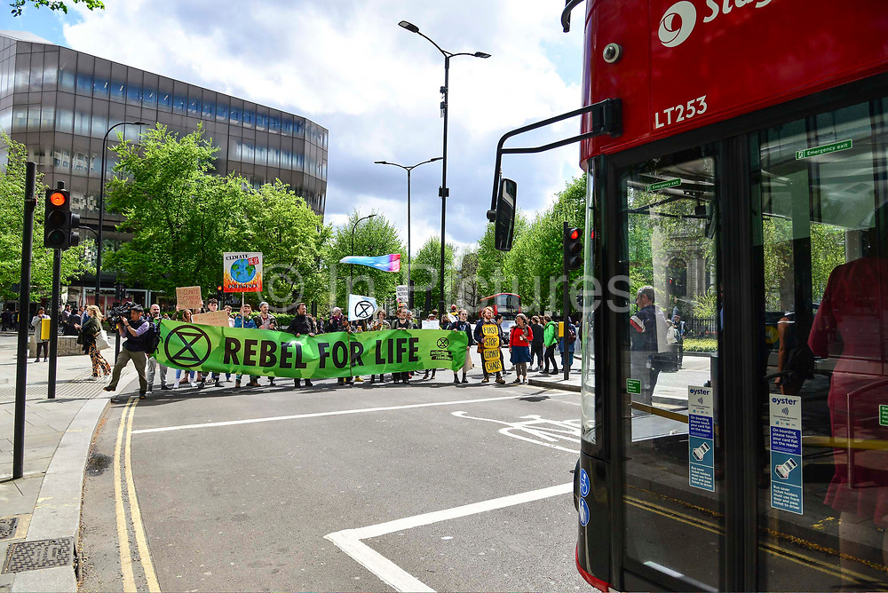 Climate change activists from the Extinction Rebellion group march and sing songs in the road blocking traffic close to St Pauls tube station demanding that the British Government acknowledge the climate crisis posed by global warming on 25th April 2019 in London, England, United Kingdom.