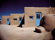 Three small adobes with blue doors sit attached to one another in the desert near Santa Fe, New Mexico