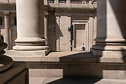 Seen through the columns of Royal Exchange, a man waits patiently for someone or something beneath the architecture of the Bank of England on Threadneedle Street in the City of London, the capitals financial district, on 8th June 2021, in London, England.