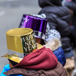Philadelphia, PA, USA - January 1, 2016: Two girls watch the Mummers parade while wearing New Years Day party hats.