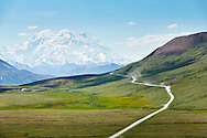 Vehicles travel down the dusty Park Road in Denali National Park, Alaska with Mt. McKinley towering in the distance.
