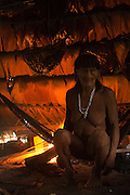 Huaorani Indian, Meñemo Bopoga making fire while sitting in her hammock.<br /> Bameno Community. Yasuni National Park.<br /> Amazon rainforest, ECUADOR.  South America<br /> This Indian tribe were basically uncontacted until 1956 when missionaries from the Summer Institute of Linguistics made contact with them. However there are still some groups from the tribe that remain uncontacted.  They are known as the Tagaeri & Taromenane. Traditionally these Indians were very hostile and killed many people who tried to enter into their territory. Their territory is in the Yasuni National Park which is now also being exploited for oil.