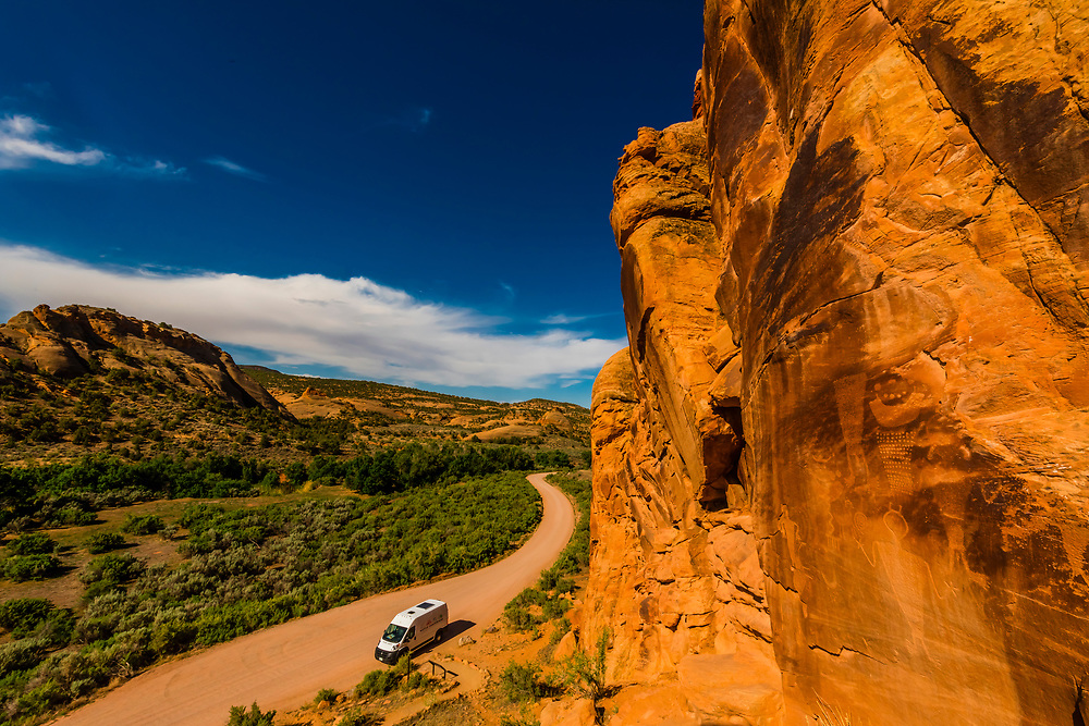 A camper van in the distance with Petroglyphs at Cub Creek created by the Fremont people who lived in the area between 550 and 1200 AD. They feature human and animal figures and abstract designs. Dinosaur National Monument, Utah USA.